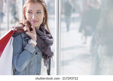 Woman carrying shopping bags while standing by store