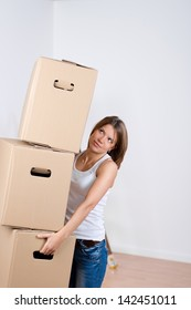 Woman carrying a stack of cardboard cartons as she packs up her household goods in preparation for moving