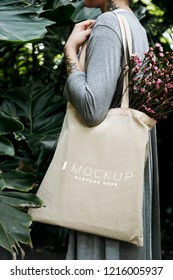 Woman carrying a tote bag mockup with flowers