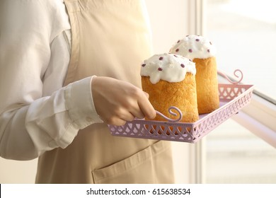 Woman carrying tray with delicious Easter cakes on light background