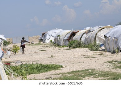 A woman carrying water, passing through on of the tent cities in Haiti.
