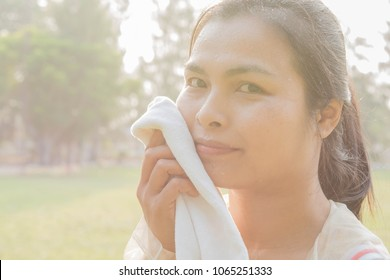 Woman carrying a white towel, drops of mineral water. spray on the face  In the morning nature