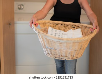 woman carrying a wicker laundry basket in home