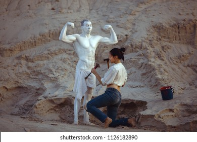 Woman carves a figure of a sports man from a stone. Sculpture of a man with a beautiful body.