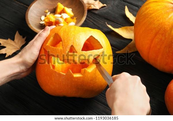Woman carving Halloween pumpkin head jack lantern on wooden table, closeup