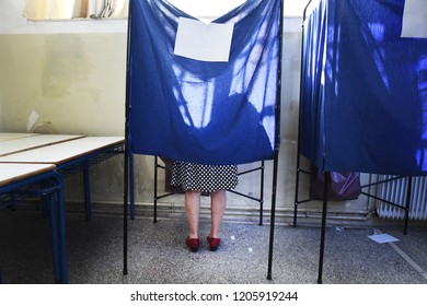A woman casts her vote inside an election booth.
