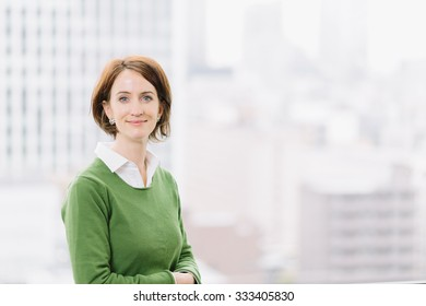 Woman in casual business attire looking at camera confidently by an office window