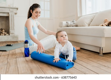 Woman in casual clothes relaxing with her son after fitness workout. They playing with water bottle and yoga mat