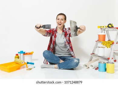Woman in casual clothes sitting on floor with putty knife, instruments for renovation apartment room isolated on white background. Wallpaper accessories for gluing painting tools. Repair home concept