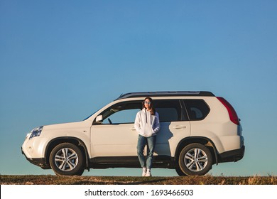 woman in casual clothes standing near white suv car