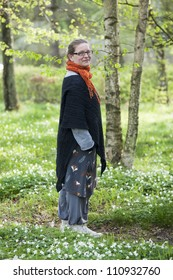 Woman in casual clothes standing on a small path in a forest. White anemones are covering the ground