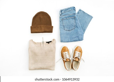 Woman casual fashion clothes and accessory set on white background. Sweater, boyfriend jeans, hat, sneakers on white background. Flat lay, top view.