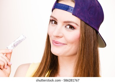 Woman casual style smiling teen girl holding a stick of chewing gum on white background. Youth style