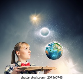 Woman in casual wear holding opened book in hands. Elements of this image are furnished by NASA