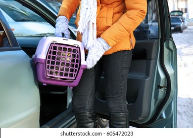 Woman with cat in carrier box near car