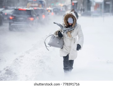 A woman is caught in a sudden gust of wind as she walks on Rene-Levesque boulevard in downtown Montreal, Quebec, Canada, after a snowstorm on Wednesday, December 13, 2017.