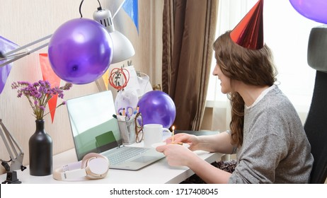 Woman celebrating her birthday through video call virtual party. Lits and blows out candle. Authentic decorated home workplace. Handheld shot with gimbal. Coronavirus outbreak 2020.