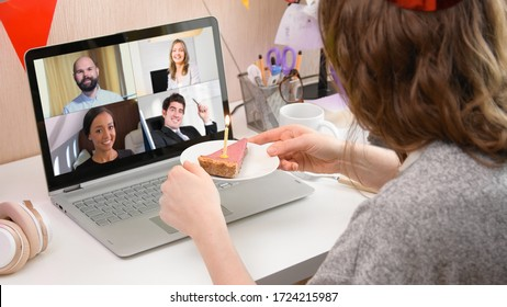 Woman celebrating her birthday through video call virtual party with friends. Lits and blows out candle. Authentic decorated home workplace. Coronavirus outbreak 2020.