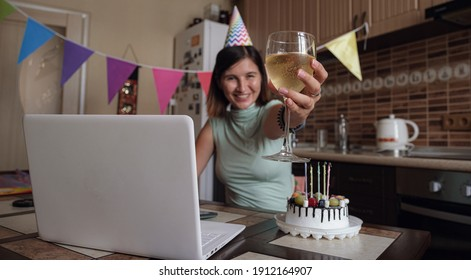 Woman celebrating her birthday through video call virtual party with friends. Lits and blows out candle. Authentic decorated home workplace. Coronavirus outbreak 2021.