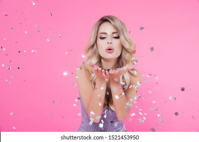 Woman celebrating New Year 2020 or Happy Birthday party. Portrait of beautiful smiling girl in shiny silver dress throwing confetti on pink background. Free space for text mockup
