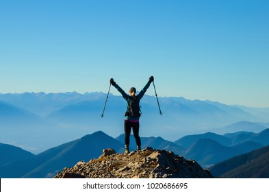 Woman celebrating reaching a mountain summit whiler hiking