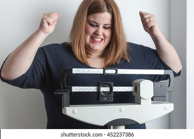woman celebrating weight loss raising her arms on the scale