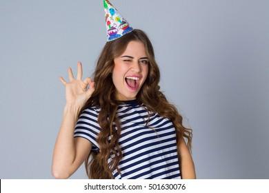 Woman in celebration cap showing okay