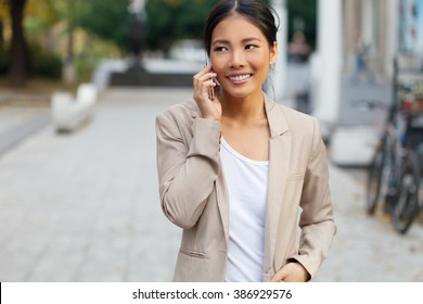 Woman with cellphone on walking on the street