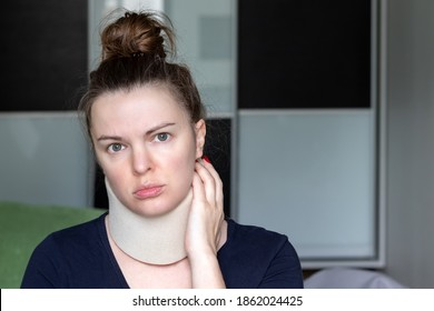 Woman with cervical surgical collar feeling pain in neck in home against a blurred background