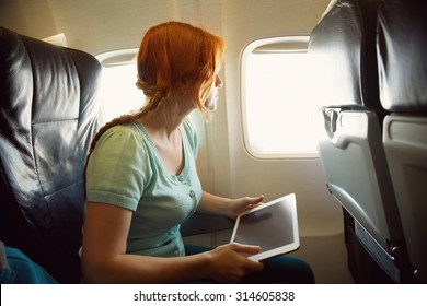 woman in the chair on board the aircraft. girl with tablet computer in an airplane. flight and travel