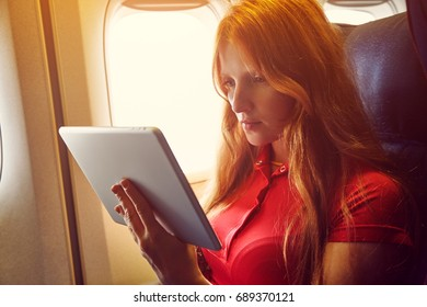 woman in a chair on board aircraft. girl with tablet computer in an airplane. flight and travel