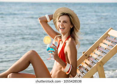 woman in chaise longue drinks coktail