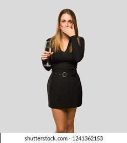woman with champagne celebrating new year 2019 covering mouth with hands for saying something inappropriate on