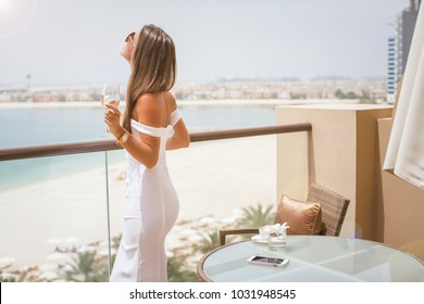Woman with champagne glass looking at view on Dubai famous travel destination. (soft focus)