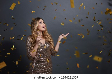Woman with champagne looking up and holding something on hand