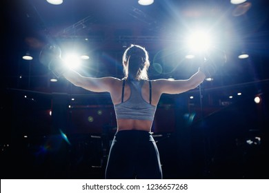 Woman champion after fight stands strong back on octagon with hands in Boxing gloves up, proudly lifted his head, spotlight. Concept of feminism