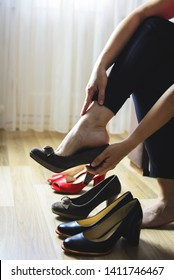 Woman changing high heels, office shoes after working day while sitting on the couch, ready to take a walk or run Girl changing shoes. Removes shoes. Tired feet of shoes. Vertical. Copy space.