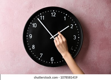 Woman changing time on big wall clock