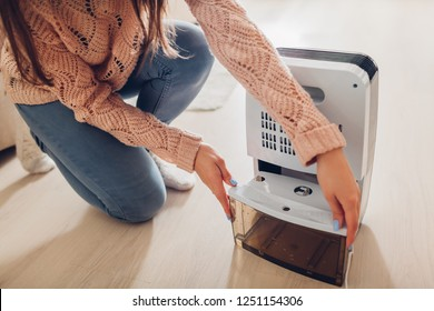 Woman changing water container of dehumidifier at home. Dampness in apartment. Modern air dryer