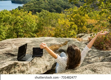 A woman charging her laptop with a solar panel at a remote work location.