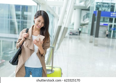Woman check flight number on mobile phone in airport