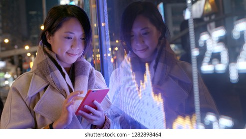 Woman check on cellphone over the stock market data screen board