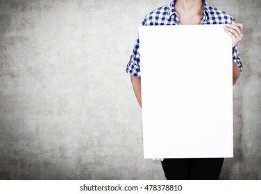 Woman in checkered shirt and black pants holding vertical poster and standing near concrete wall. Concept of advertising and goods promotion. Mock up