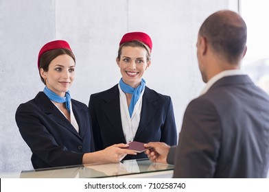 Woman in checkin counter taking passport for verification from passenger man. Happy smiling hostess at check in working with her colleague. Businessman on a business trip in airport.