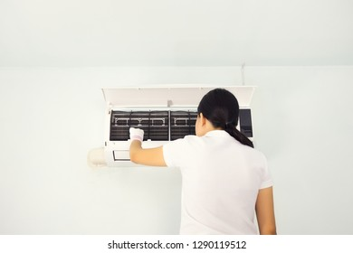 Woman checking air conditioner inside room.