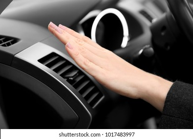 Woman checking air conditioner operation in modern car, closeup