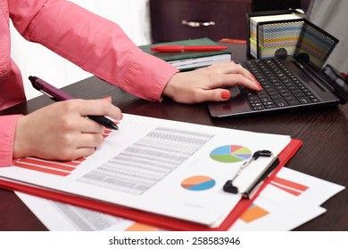 woman checking budget or payroll with laptop