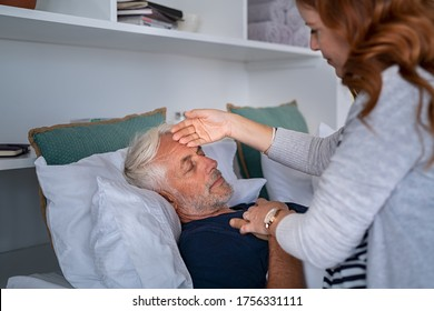 Woman checking fever temperature of senior man lying on bed. Old husband resting at home feeling sick while  while his wife assists him. Feverish man feeling the seasonal symptoms of the flu.
