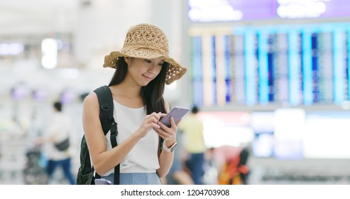 Woman checking flight number on cellphone in the airport