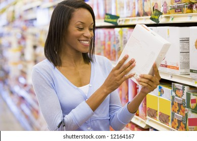 Woman checking food labelling on packet in supermarket